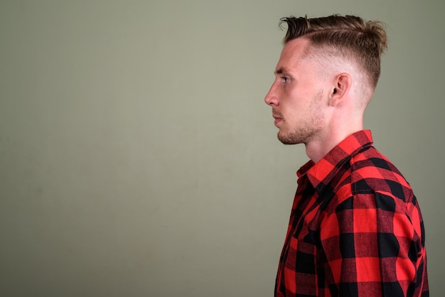 色の壁に赤い市松模様のシャツを着ている若い男