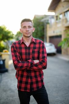 Молодой человек в красной клетчатой рубашке на улице на улице