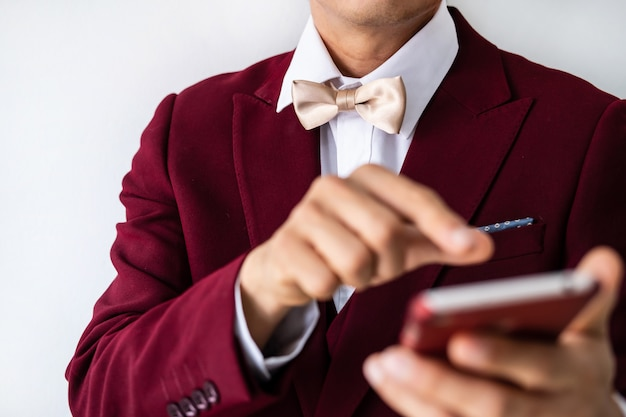 Young man wearing red suit with bow tie with smartphone