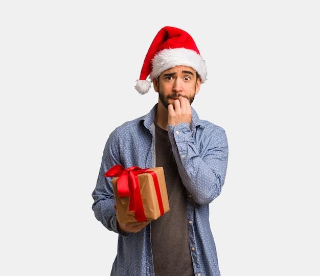 Young man wearing santa hat biting nails, nervous and very anxious