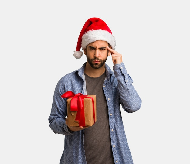 Young man wearing santa hat doing a concentration gesture