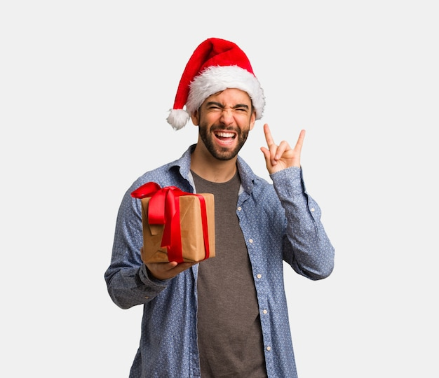 Young man wearing santa hat doing a rock gesture