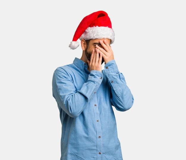 산타 모자를 쓰고 당황하고 동시에 웃고있는 젊은이