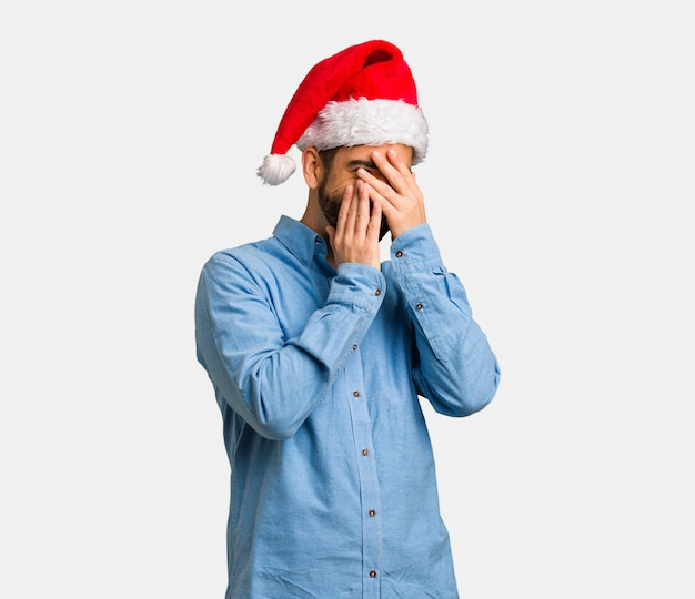 Young man wearing santa hat embarrassed and laughing at the same time