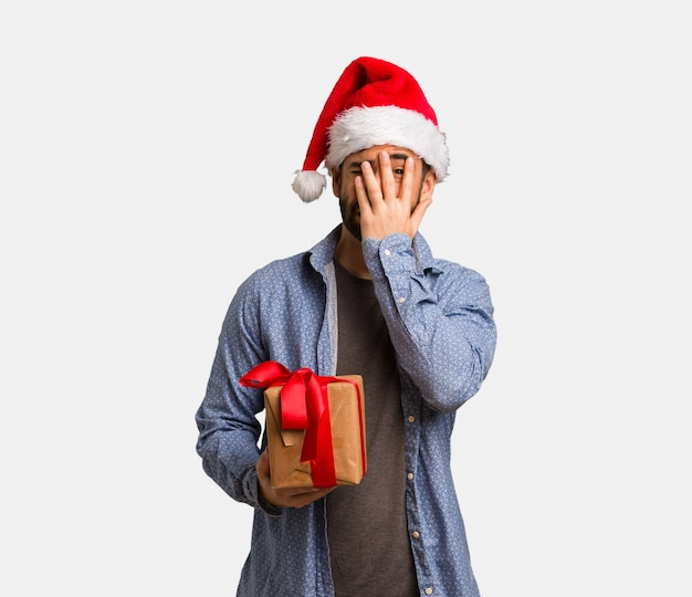 Young man wearing santa hat feels worried and scared