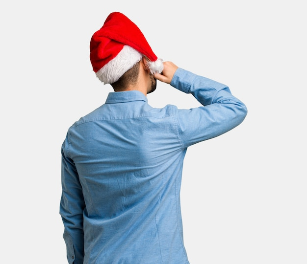 Young man wearing santa hat from behind thinking about something