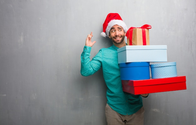 Young man wearing a santa hat holding gifts crossing fingers for having luck
