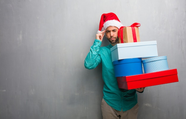 Young man wearing a santa hat holding gifts doing a concentration gesture