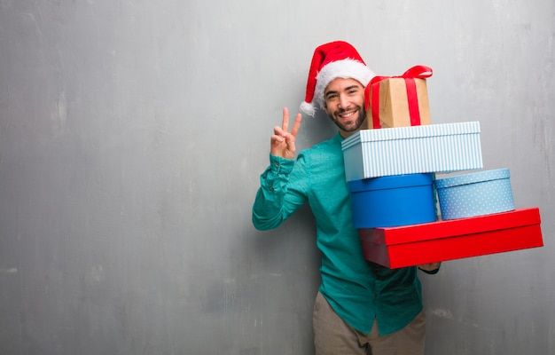 Young man wearing a santa hat holding gifts showing number two