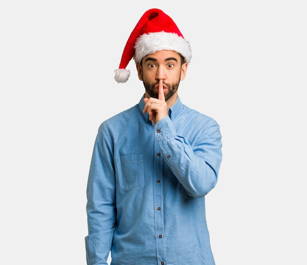 Young man wearing santa hat keeping a secret or asking for silence