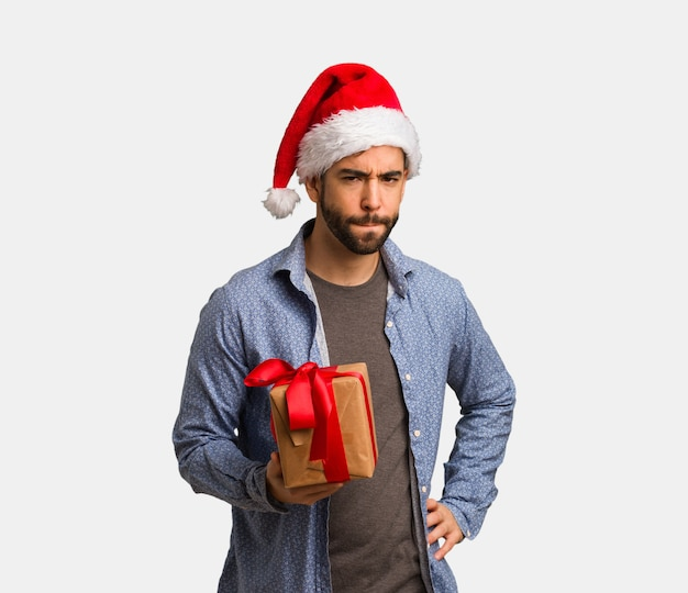 7e855b08200e8 Young man wearing santa hat scolding someone very angry