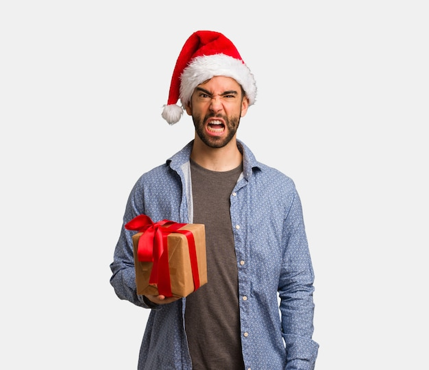 Young man wearing santa hat screaming very angry and aggressive