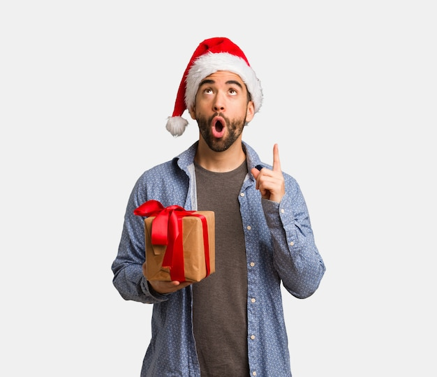 Young man wearing santa hat surprised pointing up to show something