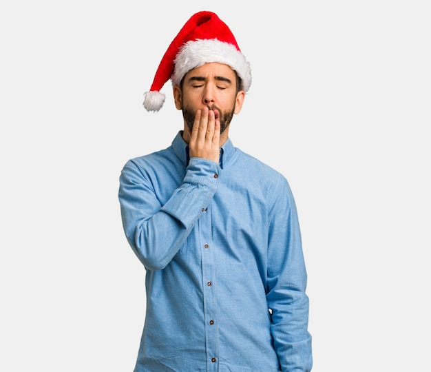 Young man wearing santa hat tired and very sleepy
