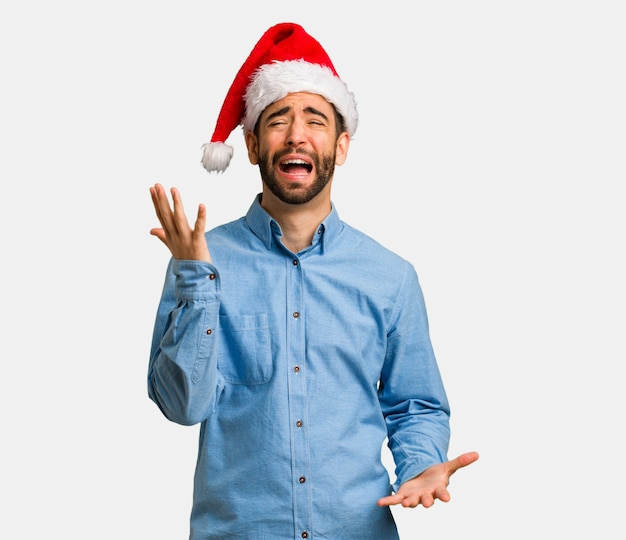 Young man wearing santa hat very scared and afraid