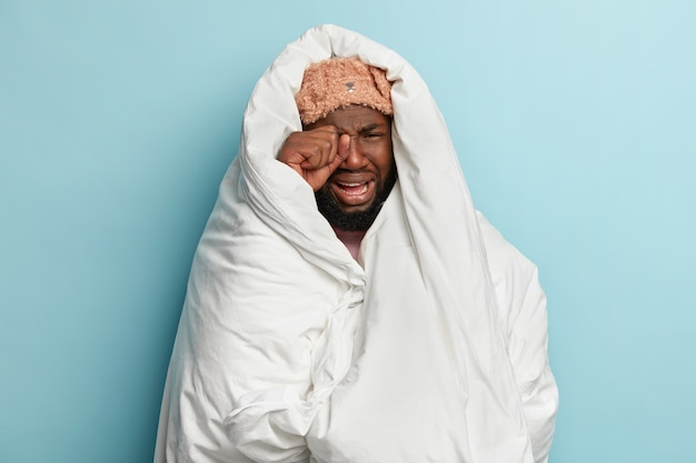 Young man wearing sleep mask and wrapped in white blanket
