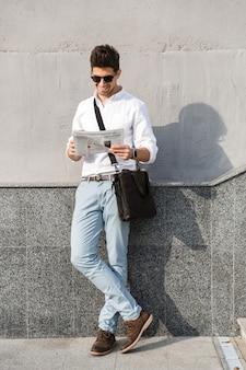Молодой человек в солнечных очках читает газету, стоя у стены на открытом воздухе