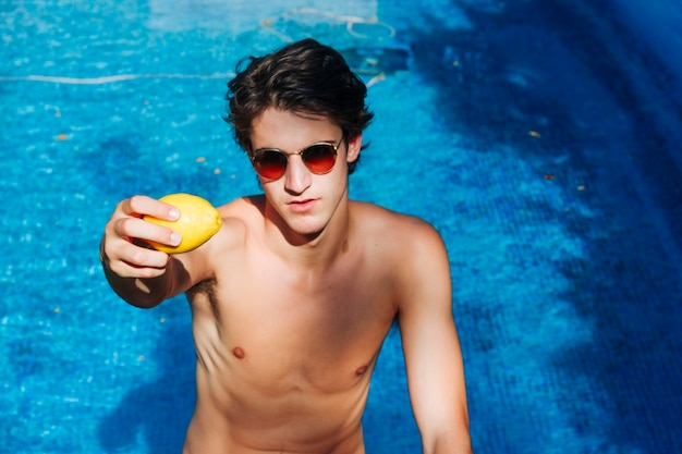 Young man wearing sunglasses showing lemon in swimming pool