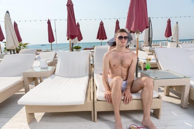 オーシャンフロントラグジュアリービーチリゾートのデッキのラウンジチェアの端に座ってサングラスをかけている若い男