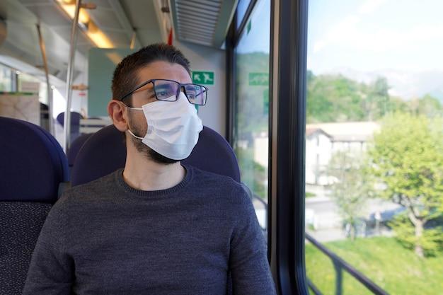 기차 창문을 통해보고 수술 마스크를 착용하는 젊은 남자