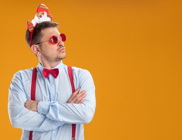 サスペンダーの蝶ネクタイを身に着けている若い男は、オレンジ色の背景の上に立っている深刻な顔で脇を見てサンタと赤い眼鏡と縁でネクタイをします