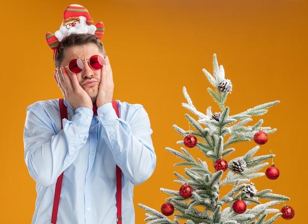 サスペンダーの蝶ネクタイを身に着けている若い男は、オレンジ色の背景に混乱し、非常に心配しているカメラを見てクリスマスツリーの横に立っているサンタと赤い眼鏡と縁でネクタイをします