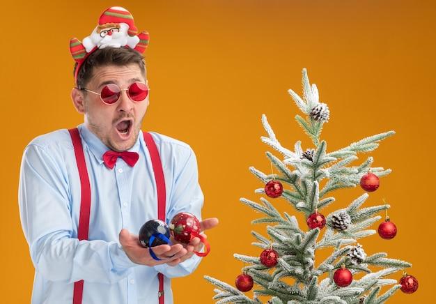 Молодой человек в подтяжках с галстуком-бабочкой в оправе с санта-клаусом и красными очками стоит рядом с елкой, выглядит смущенным и удивленным, держа игрушки для елки над оранжевой стеной
