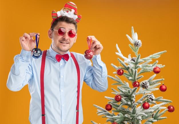 Молодой человек в подтяжках с галстуком-бабочкой в оправе с санта-клаусом и красными очками, стоящий рядом с елкой, выглядит смущенным, держа игрушки для дерева на оранжевом фоне