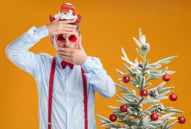 오렌지 벽 위에 다른 손으로 입을 덮고 그의 이마에 손으로 크리스마스 트리 옆에 서있는 산타와 빨간 안경 테두리에 멜빵 나비 넥타이를 착용하는 젊은 남자