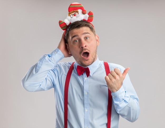 Молодой человек в подтяжках с галстуком-бабочкой в оправе с санта, глядя в камеру, изумлен и удивлен, указывая указательным пальцем в сторону, стоя на белом фоне