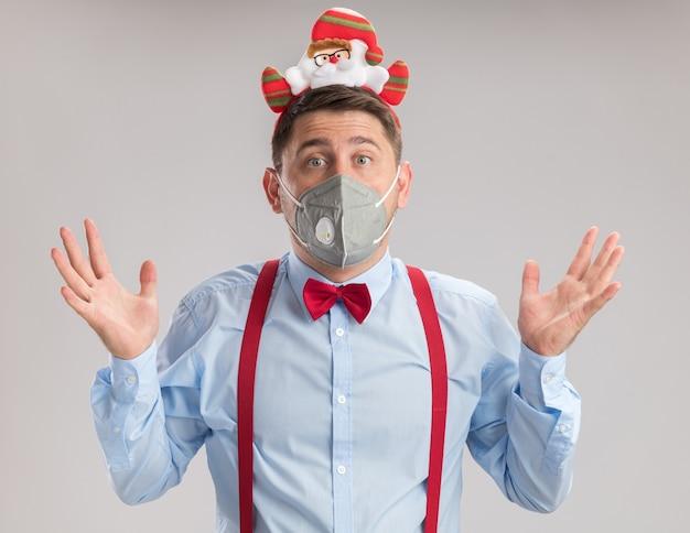 Молодой человек в подтяжках с галстуком-бабочкой в ободе с санта в защитной маске, смущенный и удивленный, смотрит в камеру с поднятыми руками, стоя на белом фоне