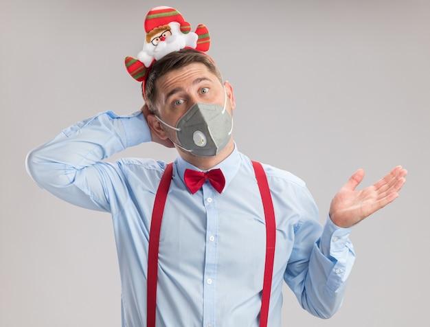 Молодой человек в подтяжках с галстуком-бабочкой в оправе с санта в защитной маске, смотрящий в камеру, путает с поднятой рукой, стоящей на белом фоне