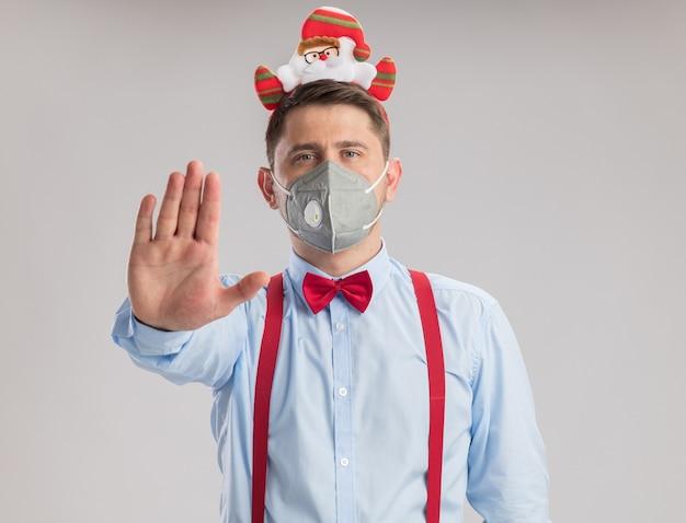 サスペンダーを身に着けている若い男は、白い背景の上に立っている手で停止ジェスチャーを作るカメラを見て保護顔のマスクを身に着けているサンタと縁に蝶ネクタイ