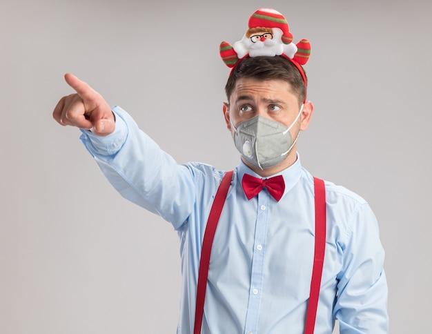 Молодой человек в подтяжках с галстуком-бабочкой в ободе с санта в защитной маске, глядя на что-то в сторону, указывая указательным пальцем, стоящим на белом фоне