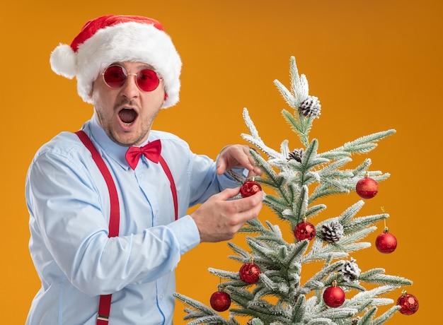 산타 모자와 빨간 안경에 멜빵을 착용하는 젊은 남자와 오렌지 배경 위에 행복하고 놀란 나무에 장난감 매달려 크리스마스 트리 근처에 서있는 빨간 안경