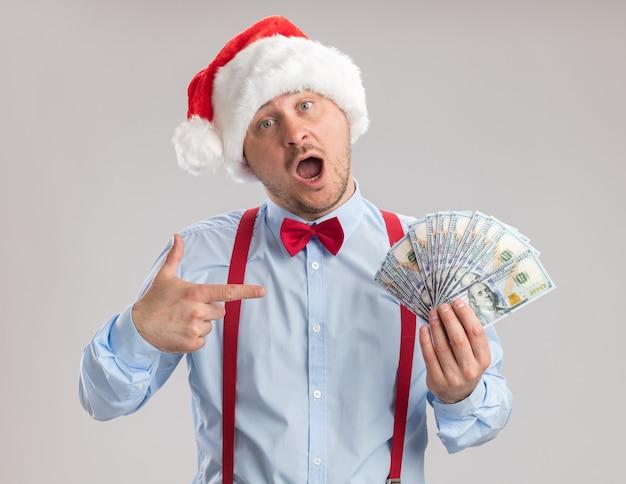Молодой человек в подтяжках с галстуком-бабочкой в шляпе санта-клауса держит деньги, удивленно указывая указательным пальцем на деньги, стоящие на белом фоне