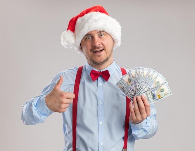 Молодой человек в подтяжках с галстуком-бабочкой в шляпе санта-клауса держит деньги, показывая большие пальцы руки вверх, счастливым и удивленным, глядя на камеру, стоящую на белом фоне