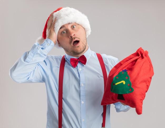 Молодой человек в подтяжках с галстуком-бабочкой в шляпе санта-клауса держит сумку санта-клауса, полную подарков, глядя в камеру, изумленный и удивленный, стоя на белом фоне