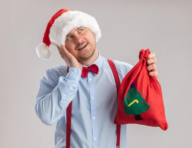 Молодой человек в подтяжках с галстуком-бабочкой в шляпе санта-клауса держит сумку санта-клауса, полную подарков, глядя вверх счастливым и позитивным, улыбаясь, стоя на белом фоне