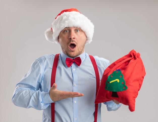 サスペンダーの蝶ネクタイを身に着けている若い男は、白い背景の上に立って驚いて驚いた彼の手に腕を提示する贈り物でいっぱいのサンタクロースのバッグを持ってサンタの帽子をかぶっています