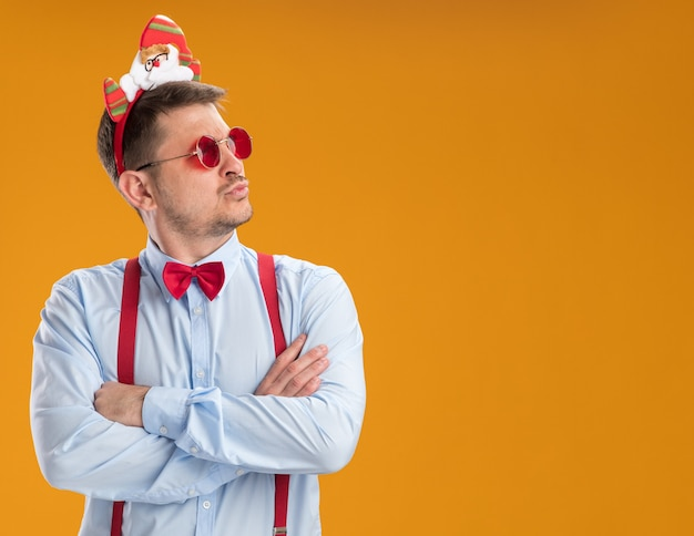 Young man wearing suspenders bow tie in rim with santa and red glasses looking aside with serious face standing over orange background
