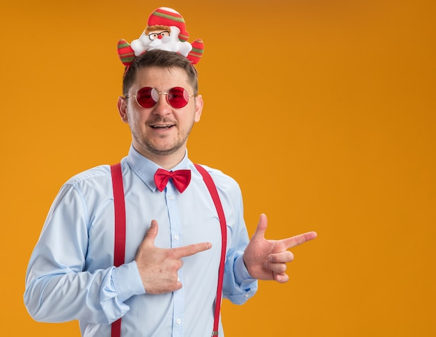 Young man wearing suspenders bow tie in rim with santa and red glasses pointing with index fingers to the side smiling with happy face standing over orange background