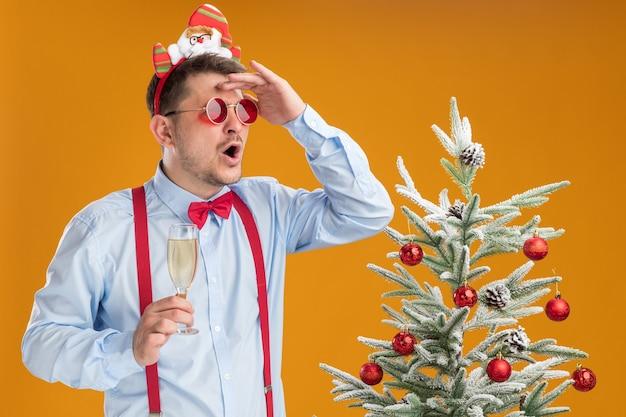Giovane uomo che indossa bretelle farfallino nel cerchio con babbo natale e occhiali rossi in piedi accanto all'albero di natale con in mano un bicchiere di champagne guardando lontano con la mano sopra la testa sulla parete arancione