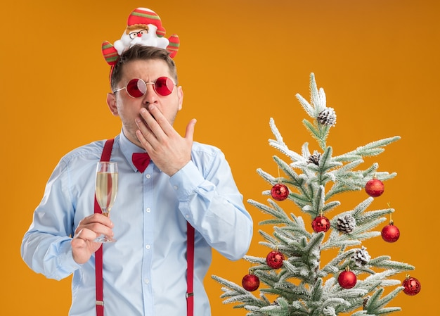 Young man wearing suspenders bow tie in rim with santa and red glasses standing next to christmas tree holding glass of champagne