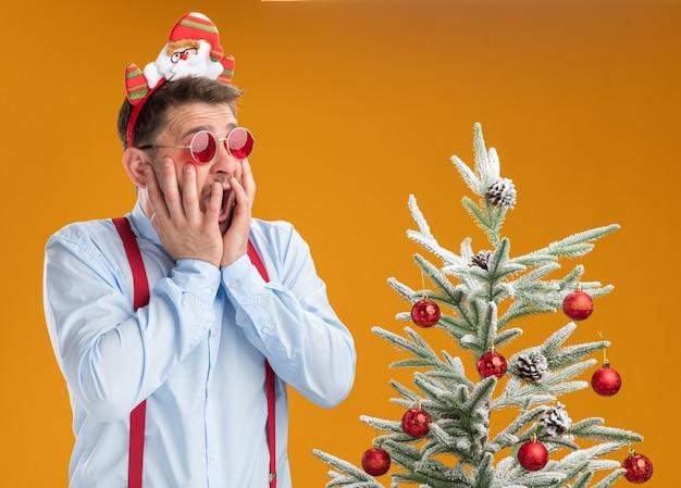Giovane uomo che indossa bretelle bow tie nel cerchio con santa e occhiali rossi in piedi accanto all'albero di natale guardando albero in preda al panico su sfondo arancione