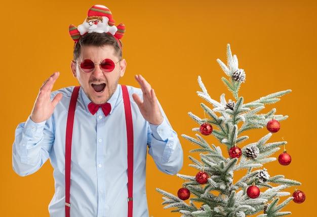 Giovane uomo che indossa bretelle farfallino nel cerchio con babbo natale e occhiali rossi in piedi accanto all'albero di natale che grida in preda al panico oltre la parete arancione