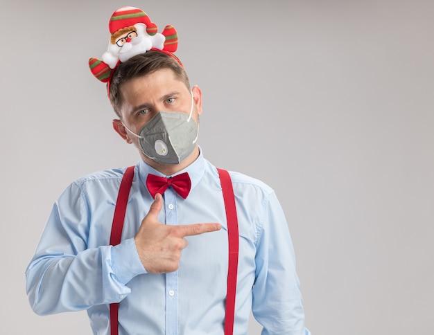 Giovane uomo che indossa bretelle farfallino in cerchio con santa che indossa una maschera facciale protettiva guardando la telecamera che punta con il dito indice sul lato in piedi su sfondo bianco