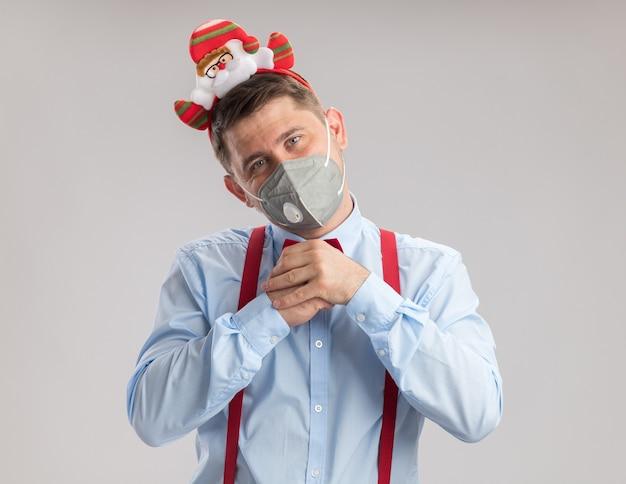 Giovane uomo che indossa bretelle farfallino in cerchio con santa che indossa maschera facciale protettiva guardando la fotocamera con faccia felice che tiene le mani insieme in piedi su sfondo bianco