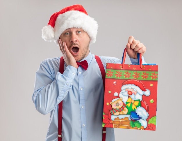 Young man wearing suspenders bow tie in santa hat holding cash standing over white background