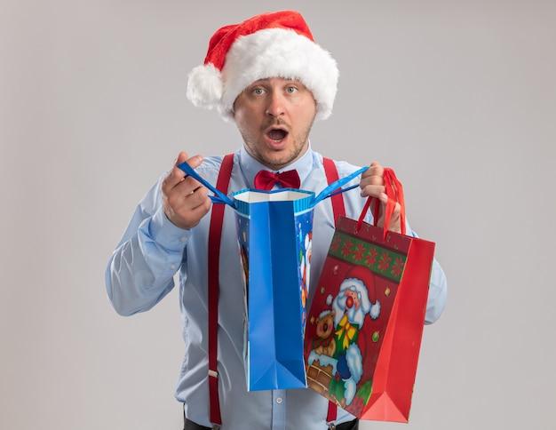 Giovane uomo che indossa bretelle farfallino in cappello di babbo natale che tiene sacchetti di carta regalo guardando la telecamera stupito e sorpreso in piedi su sfondo bianco